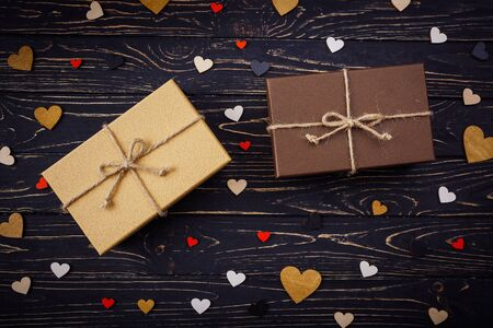 Two brown gift boxes on a wooden background with a bow of a simple rope on wood backgraund. Small decorative wooden hearts near box Zdjęcie Seryjne