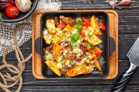 Concept promotional flyer. Baked potatoes with meat, tomatoes, greens and cheese. On a black wooden background. Flay lay. Top view Zdjęcie Seryjne