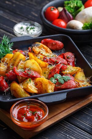 Potato baked with sausages along with white and red sauce. On a black wooden background