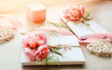 Gift boxes wrapped with simple white craft paper and bouquet of roses. Little pink giftbox and satin pink ribbon and wooden heart. Selective focus