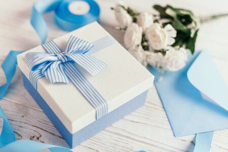 Gift box with blue ribbon and bow. Simple composition with present wrapped. Giftwrap, silk ribbon. Floral decor elements. Zdjęcie Seryjne - 128957834