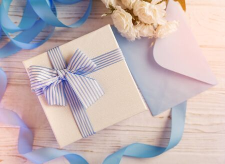 Gift box with blue ribbon and bow. Simple composition with present wrapped. Giftwrap, silk ribbon. Floral decor elements.