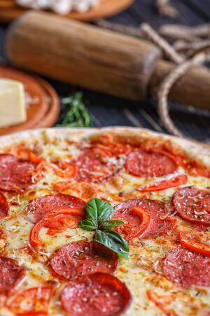 Aromatic pizza with sausage and tomatoes is decorated with basil. Concept promotional flyer Stockfoto