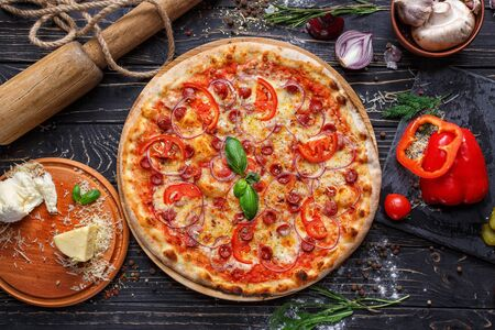 Aromatic pizza with hunting sausages, onions and tomatoes. As package design element. Pizza on a black wooden background among spices Stockfoto