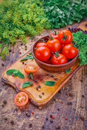 A plate of fragrant tomatoes on a wooden board with mint. Fresh vegetables on the table Zdjęcie Seryjne