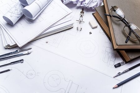 Books, glasses, pencil, compass and rolls of drawings on the details of industrial drawings. The set of elements reflecting the concept of engineering and design.