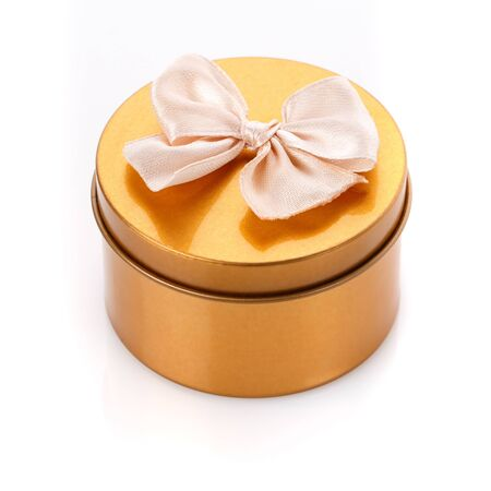 Single round gold gift box with bow on white background. Modern present for any holiday, christmas, valentine or birthday Stockfoto