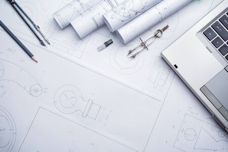 Compass and several drawing tools available in the drawings. Architectural prints and print rolls and a drawing instruments on the worktable. Stockfoto