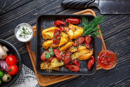 Poster for Restaurants. Potato baked with sausages along with white and red sauce. On a black wooden background. Flay lay. Top view Zdjęcie Seryjne - 128807815
