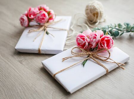 Natural style handcrafted gift box on wooden table. Handmade present box wrapped in white paper. Floral decor elements. Gift wrapping. Greeting for Valentines Day, Womans Day, Mothers Day,
