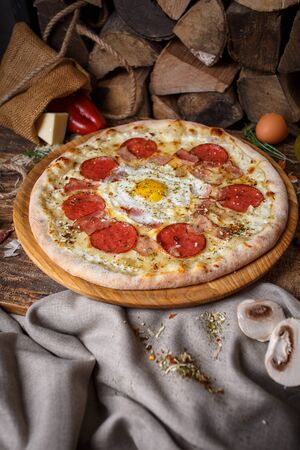 Pizza with egg against the background of firewood and sack. Poster for Restaurants or pizzerias Imagens
