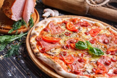 Aromatic pizza with sausage and tomatoes is decorated with basil. Poster for Restaurants or pizzerias. Pizza on a black background