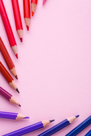 A group of bright wooden pencils on a pink background. Bright color palette of crayons on the table. Top view, flat lay. copyspace Stock fotó