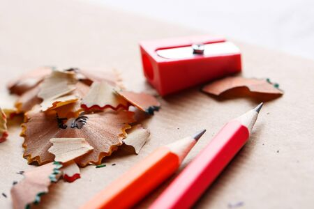 Red sharpener with pencils on the table. Concept of education or back to school