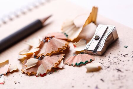 Sharpener, shavings and pencil on a white background. selective focus.