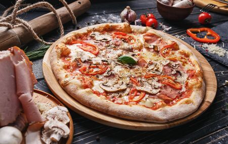 A composition of mushroom pizza and ingredients for its preparation. Pizza on a black background. As package design element