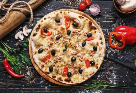 Exquisite pizza with fish, olives and onions. Poster for Restaurants or pizzerias. Pizza on a black wooden background among spices