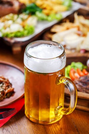 A glass of light beer on the background of a table with snacks. A glass of light beer with foam on a wooden table in the pub Stock fotó - 133402746