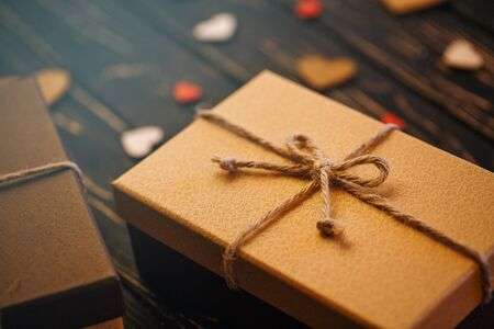 Two brown gift boxes on a wooden background with a bow of a simple rope on wood backgraund. Mother's day. Women's day. Valentine's day, Birthday greeting concept background.