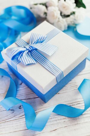 Gift box with bow. Blue satin ribbons and postal envelope. Flowers in the background.