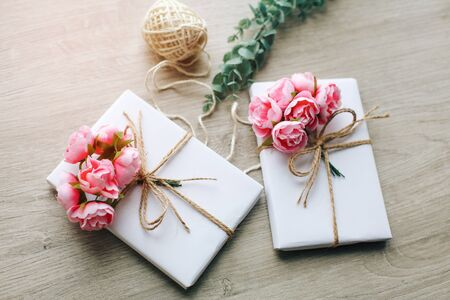 Handmade present box wrapped in paper with branch of roses. Eucalyptus branch and rustic hemp cord spools on background