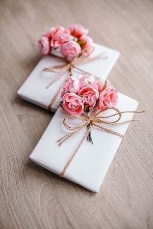 Couple of gift boxes wrapped with simple white craft paper and decorated with bouquet of roses and bunch of eucalyptus. Reklamní fotografie