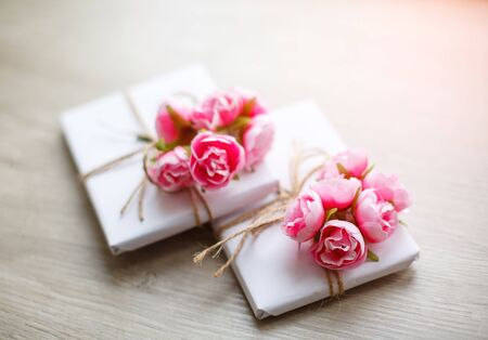 Natural style handcrafted gift box on wooden table. Handmade present box wrapped in white paper. Floral decor elements.