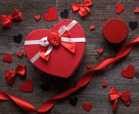 Heart shaped gift box with felt hearts and satin bow on a wooden background. Stock fotó