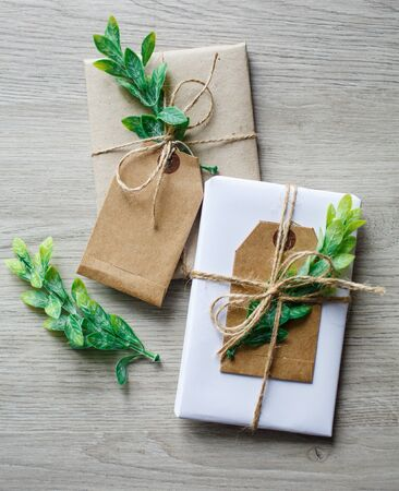 Composition with natural style handcrafted gift boxes, floral decor elements and rustic twine bow on wooden background.