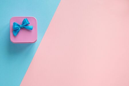 Simple composition of pink gift box with a blue bow on a blue and pink background. Pastel tone picture.