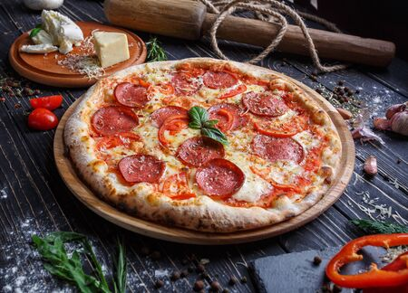 Aromatic pizza with sausage and tomatoes is decorated with basil Stock fotó - 133402898