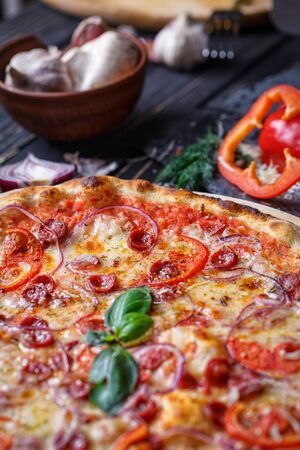 Aromatic pizza with hunting sausages, onions and tomatoes near with vegetables Stock fotó