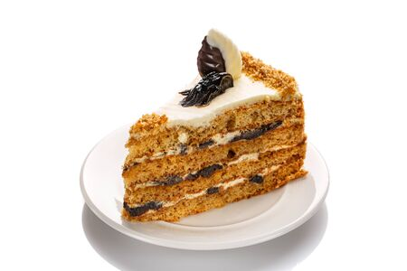 A piece of cake with honey and prunes, highlighted with a white background Stock Photo