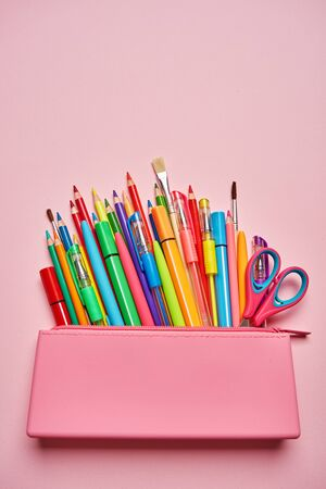Bright stationery in the pencil case is lying on a pink background. Group of school supplies on table. Flat lay. copyspace
