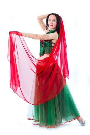 The girl is froze in a dance position. The girl in a green dress and with a red scarf on a photo studio. Isolated on a white background