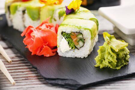 Japanese cuisine. Sushi set on black stone board on wooden table. Sushi, Wasabi and ginger close up.