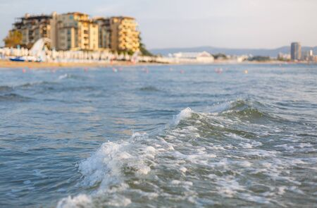 Sea waves on a warm summer day. Sunny beach. Tourist hotel on the background Archivio Fotografico - 133942671
