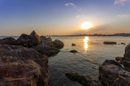 A magical sunset above the city by the sea. Rocks in the foreground