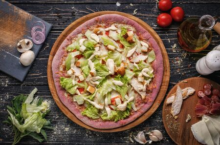 Top view of pizza with chicken meat, tomatoes, bread and lettuce on wooden plates. Italy food. Ingredient composition for pizza. Flat lay. Stock fotó