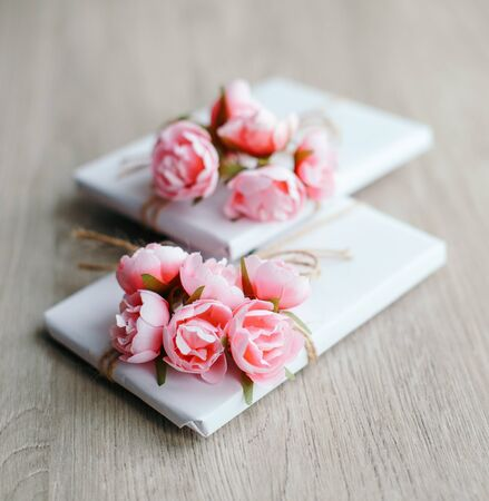 Couple of gift boxes wrapped with simple white craft paper and decorated with bouquet of roses and bunch of eucalyptus. Rustic decor.