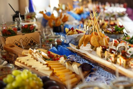 Tasty snack. Buffet with cold appetizers and many types of cheese on wooden boards.