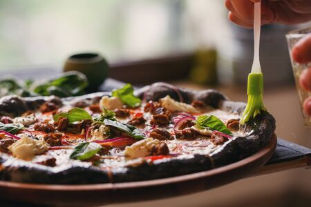 Delicious background. The cook lubricates the pizza with ham and basil with olive oil. Close up