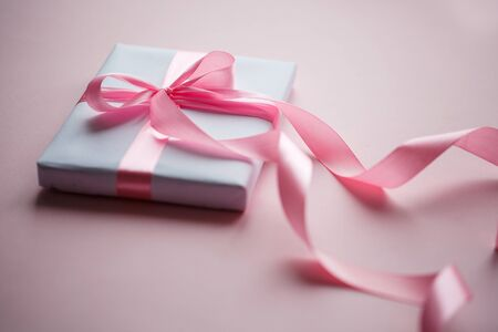 Gift box wrapped in white paper with pink ribbon on pink background. Stock fotó