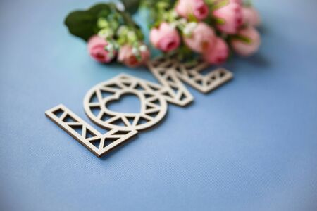 Wooden love inscription. Love background. Love and flowers on a blue background