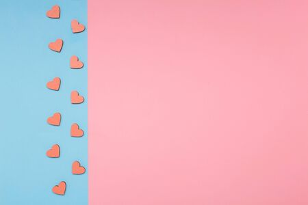 Flat lay love background. Pink and blue background. Pink wooden hearts on a blue background. Love and holiday greeting concept background. Symbol of love.
