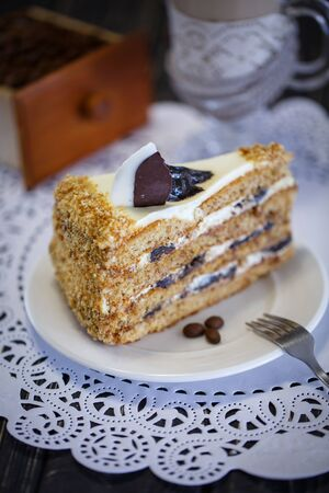 Cake with honey and prunes on a white plate. Birthday Cake.