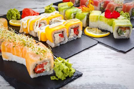 Sushi varieties on a black metal board. Japanese traditional dishes. Rice rolls with varieties of fish, cheese and vegetables. Restaurant serving. Close up. Stock fotó