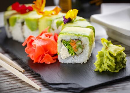 Tasty sushi set. Japanese traditional dishes. Rice rolls. Stuffed with fish, vegetables and cheese. Filed on a black metal board with ginger and wasabi. Close up. Stock fotó