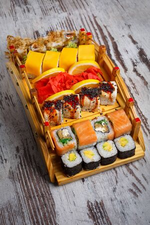 Traditional Japanese cuisine. A great set of different types of sushi. Restaurant presentation of food. Simple wooden background.