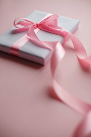 White gift box with pink bow on a pink background. Holiday concept